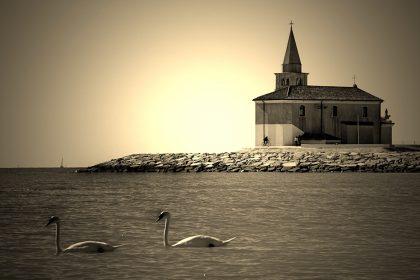 Kirche Madonna dell'Angelo am Strand von Caorle mit Schwänen im Meer
