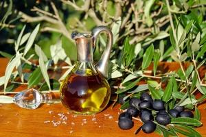 Schwarze Oliven mit Olivenzweigen auf Tisch mit Olivenöl